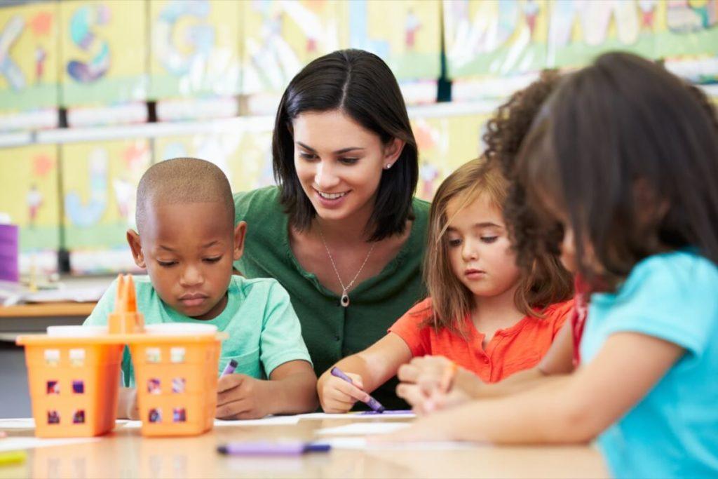 Staff helping kids use crayons.