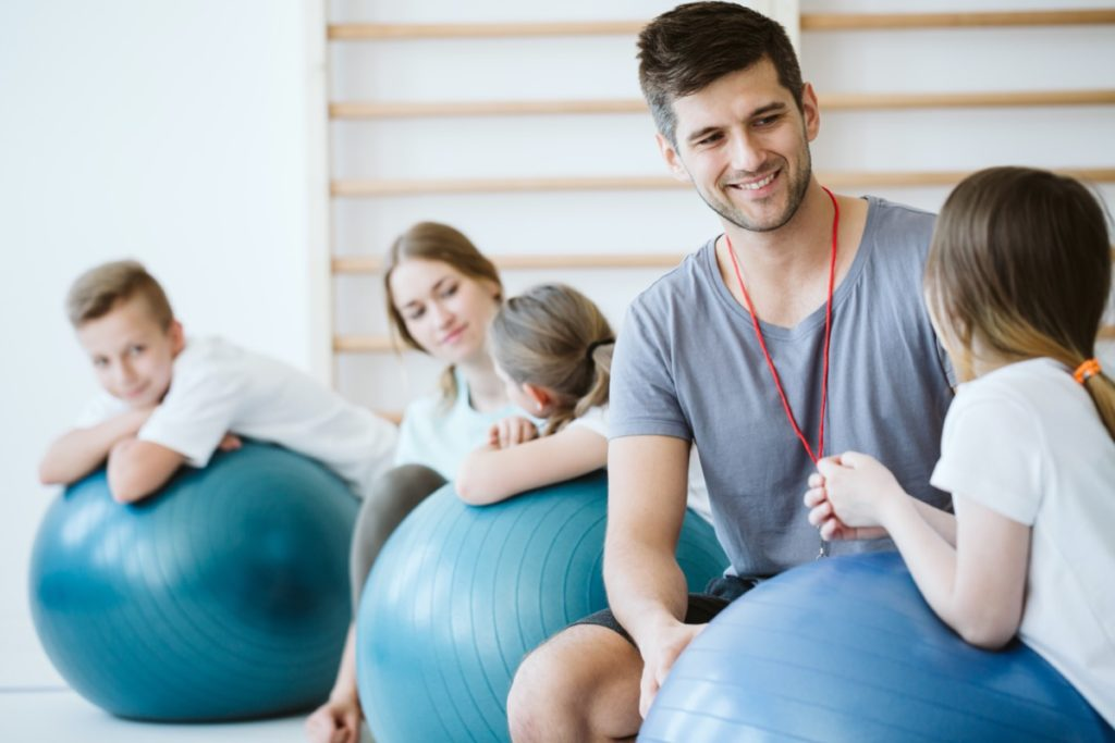 Staff member with kids on large exercise balls