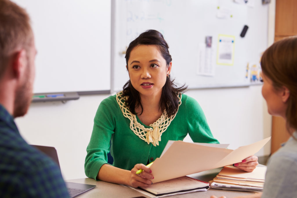 teacher-at-desk-talking-to-adult-education-students